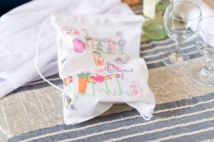 Shari Klein preserves the broken glass from her Jewish wedding in the pictured bag, which features an illustration by her husband's children depicting the day on which their dad would marry his new wife. Credit: Courtesy Shari Klein.